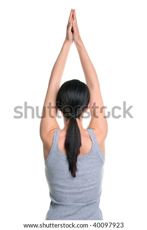 Rear view of a brunette woman doing yoga with her arms outstretched above her head, isolated on a white background. - stock photo