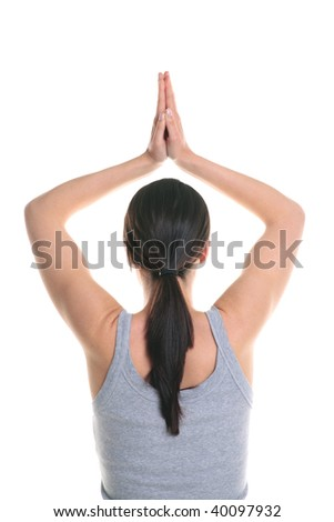 Rear view of a brunette woman doing yoga with her hands above her head, isolated on a white background. - stock photo