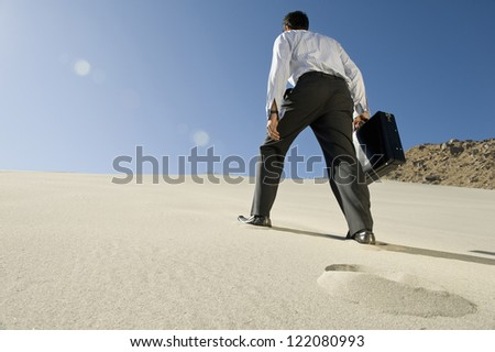 Rear view of a business man walking with briefcase on desert - stock photo