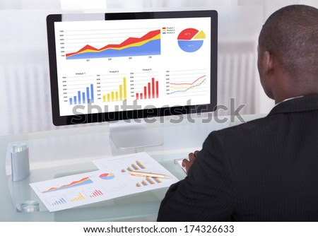 Rear View Of A Businessman Analyzing Graph On Computer - stock photo