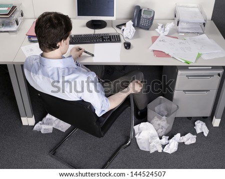 Rear view of a businessman brainstorming at office desk - stock photo