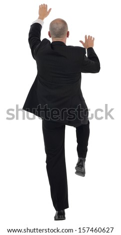 rear view of a businessman climbing isolated on a white background - stock photo