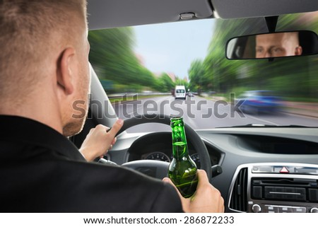 Rear View Of A Businessman Drinking Beer While Driving Car - stock photo