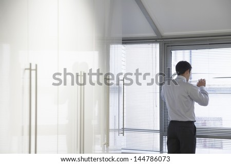 Rear view of a businessman looking out of the window through blinds - stock photo