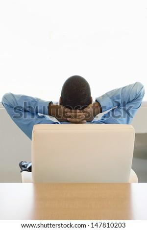 Rear View of a businessman sitting on chair with hands behind head - stock photo