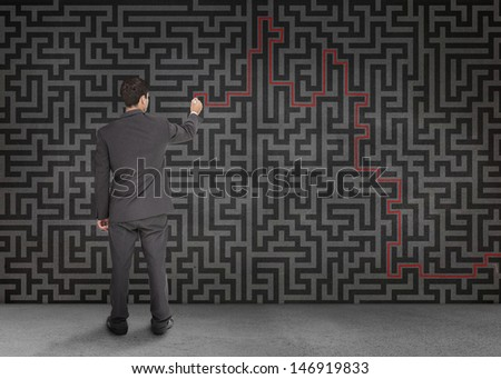 Rear view of a businessman writing a red line through black maze on a wall - stock photo