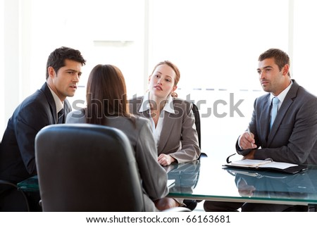 Rear view of a businesswoman being interviewed by three executives sitting around a table - stock photo