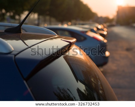 Rear view of a car on sunset, parking - stock photo