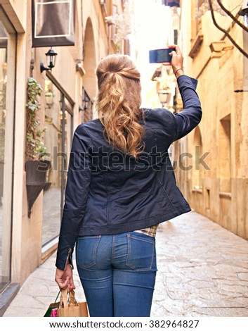 Rear view of a caucasian teenager tourist walking in a picturesque city street holding up her smart phone taking pictures on holiday, sunny outdoors. Young person using technology, tourist lifestyle. - stock photo