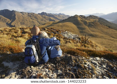 Rear view of a couple embracing while looking at hills - stock photo