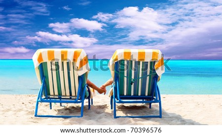 Rear view of a couple on a deck chair relaxing on the beach - stock photo