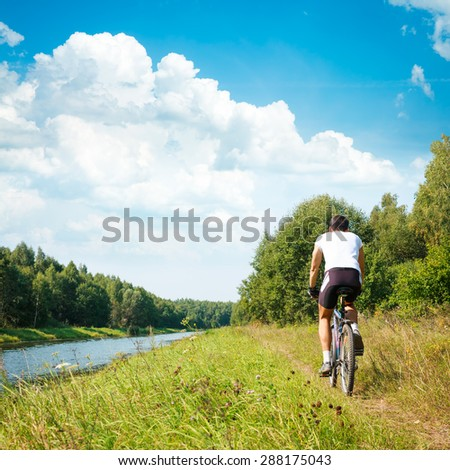 Rear View of a Cyclist Riding a Bike on River Bank. Healthy Lifestyle Concept. Square Photo with Copy Space. - stock photo