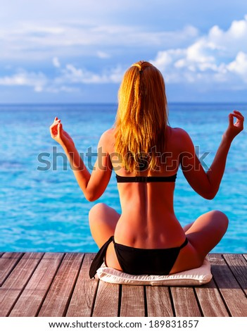 Rear view of a girl meditating, doing yoga exercise on seashore, sitting in lotus position and enjoying peaceful view, summer vacation, zen balance concept - stock photo