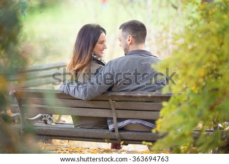 Rear view of a happy young couple sitting on a park bench - stock photo