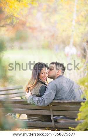 Rear view of a happy young couple sitting on a park bench, young woman looking to camera over the shoulder while her boyfriend is kissing her  - stock photo