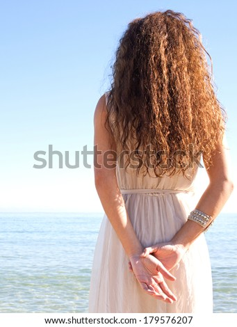 Rear view of a healthy young woman relaxing on a beach during a sunny summer day on holiday, standing against a bright blue sky. Outdoors beauty and well being lifestyle. - stock photo