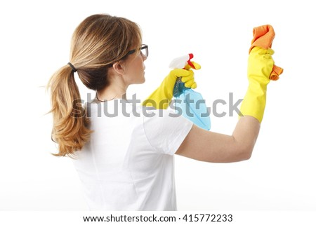 Rear view of a housekeeper woman holding in her hand a spray bottle and a cleaning sponge while standing at isolated background.  - stock photo