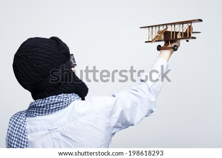 Rear view of a kid playing with toy airplane against gray background - stock photo