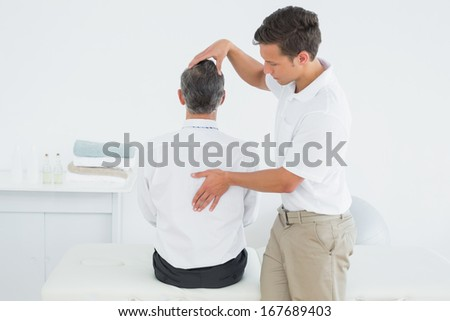 Rear view of a male chiropractor examining mature man at office - stock photo