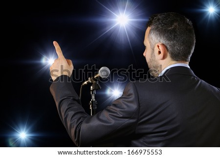 Rear view of a male public speaker speaking at the microphone, pointing, in the spotlights, symbol of leadership and international conferences - stock photo