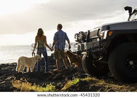 Rear view of a man and woman holding hands and relaxing with their dogs at a beach with the edge of an SUV visible in the foreground. Horizontal format. - stock photo