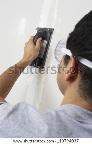Rear view of a man applying putty on wall - stock photo