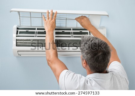 Rear View Of A Man Cleaning Air Conditioning System - stock photo