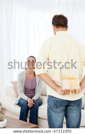 Rear view of a man hiding a gift for his girlfriend in the living room - stock photo
