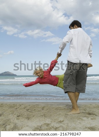 Rear view of a man playing with his daughter - stock photo