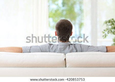 Rear view of a man relaxing sitting on a sofa at home and looking outdoors through the window at home - stock photo