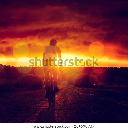 Rear View of a Man Riding a Bicycle at Sunset. Healthy Lifestyle and Travel Concept. Dramatic Sky. Toned Photo with Bokeh. Copy Space. - stock photo