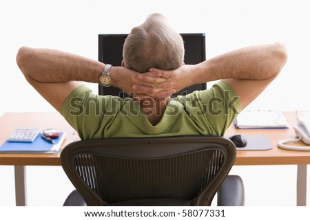 Rear view of a man seated at a desk in front of a laptop. He is sitting back in his chair with his hands behind his head. Horizontal shot. - stock photo