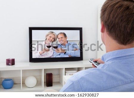 Rear View Of A Man Sitting On Couch Watching Television - stock photo