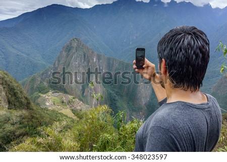 Rear view of a man taking picture of Machu Picchu, Cusco Region, Urubamba Province, Machupicchu District, Peru - stock photo
