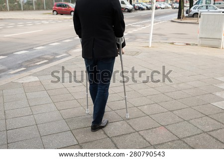 Rear View Of A Man Walking On Street Using Crutches - stock photo