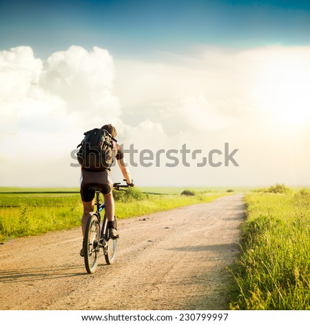 Rear View of a Man with Backpack Riding a Bicycle on Beautiful Nature Background. Healthy Lifestyle and Travel Concept. Instagram Styled Toned Photo. Copyspace. - stock photo