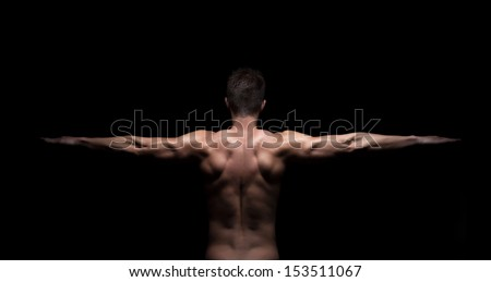 Rear view of a muscular man with arms stretched out on black background - stock photo