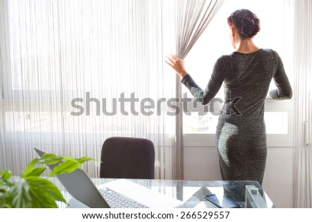 Rear view of a office business woman standing looking out a bright window in her home office desk, thoughtful and contemplative, interior. Aspirational professional woman using technology, indoors. - stock photo