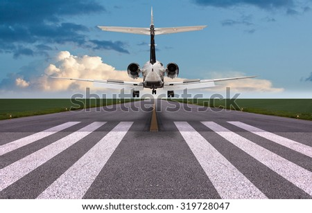 Rear view of a private jet landing - stock photo