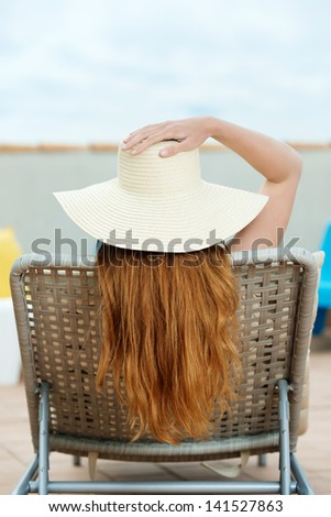 Rear view of a redhead woman in straw hat sitting on deck chair at roof terrace - stock photo