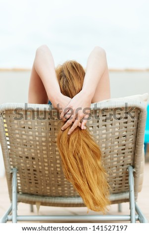 Rear view of a redhead woman on deck chair at roof terrace - stock photo