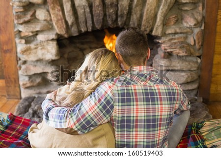 Rear view of a romantic young couple sitting in front of lit fireplace - stock photo