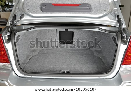 Rear view of a sedan car with open trunk - stock photo