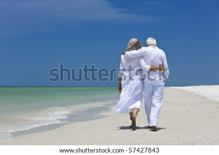Rear view of a senior man and woman couple walking arms around each other on a deserted tropical beach with bright clear blue sky - stock photo