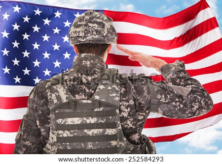 Rear View Of A Soldier Saluting American Flag - stock photo
