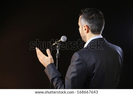 Rear view of a speaker speaking at the microphone - stock photo