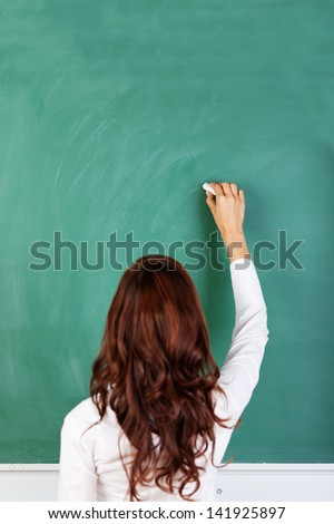 Rear view of a student or teacher with long brunette hair writing on a blank green blackboard or chalkboard with copyspace - stock photo