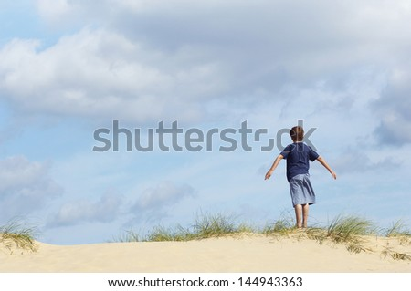 Rear view of a young boy standing on sand dune in wind with arms outstretched - stock photo