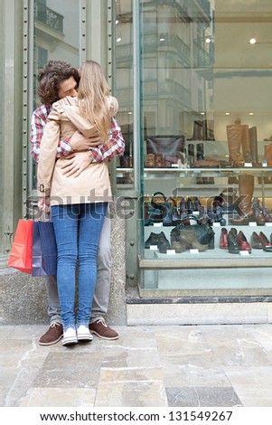 Rear view of a young couple hugging in a destination city while standing in the shopping district near a luxury quality shoe store, outdoors. - stock photo