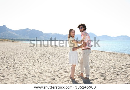 Rear view of a young couple walking together, turning to look at camera, on a sunny sandy beach on holiday, blue sky and sunshine, enjoying sea vacation outdoors. Travel lifestyle, coastal exterior. - stock photo